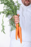 Closeup of a bunch of raw carrots being held by a chef in whites — Stock Photo