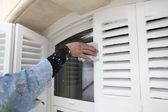 Man sandpapering shutters — Stock Photo