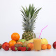 Variety of fruit behind glass of juice — Stock Photo #18473425