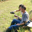 Couple drinking red wine in a vineyard — Stock Photo