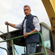 Farmer driving large vehicle - Stock Photo