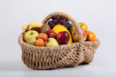 Wicker basket full of fresh fruit at a slight angle — Stock Photo