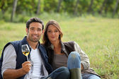 Couple having a glass of wine by a vineyard — Stock Photo