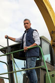 Farmer driving large vehicle — Stock Photo
