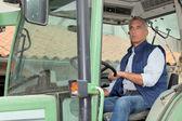 Farmer driving tractor — Stock Photo