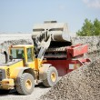 Digger moving gravel — Stockfoto