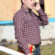 Stock Photo: Construction site supervisor talking on his cell