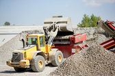 Digger moving gravel — Stock Photo