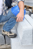 Construction worker kneeling by concrete blocks — Stock Photo