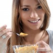 Stock Photo: Young girl eating cereals