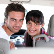 Stock Photo: Couple looking over their shoulders in a car