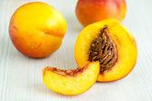 Fresh peaches on white table — Stock Photo