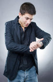 Young man looking at his watch — Stockfoto