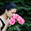 Young woman smelling roses — Stock Photo #48062511