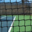 Tennis Court Net with the Court Beyond - Stock Photo