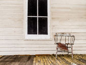 Old dilapidated porch and chair — Stok fotoğraf
