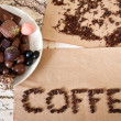 "Still life of chocolate, coffee beans, candy, the word ""coffee"" — Stock Photo"