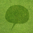 Comment icon on green grass texture and background — Stock Photo #12179485