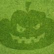 Foto Stock: Halloween pumpkin on green grass texture and background