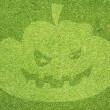 Halloween pumpkin on green grass texture and background — Stok fotoğraf