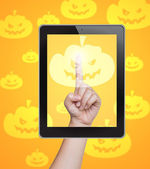 Hand pushing pumpkin button of tablet on a touch screen — Stock Photo