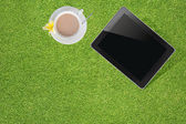 Tablet with teacup on grass background — Stock Photo