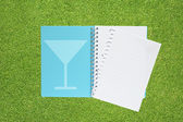 Book with drink icon on grass background — Stok fotoğraf