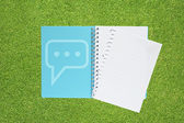 Book with comment icon on grass background — Stock Photo