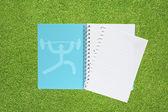 Livro com ícone de peso do esporte em fundo de grama — Fotografia Stock