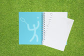 Book with Sport tennis icon on grass background — Stock Photo