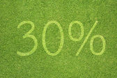 Percent icon on green grass texture and background — Stock Photo