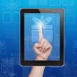 Hand pushing gift box button of tablet on a touch screen — Stock Photo #17594953