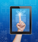 Hand pushing gift box button of tablet on a touch screen — Stock Photo