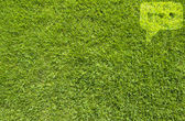Comment icon on green grass background — Stock Photo