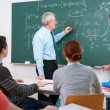 Stock Photo: Teacher with students in classroom