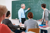 Teacher with students in classroom — Stockfoto