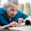 Senior woman counting money - Stock Photo