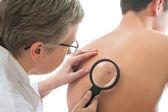 Dermatolog analizuje kret — Zdjęcie stockowe