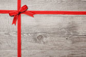 Red ribbon and bow over wooden background — Stock Photo