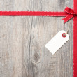 Red ribbon and bow with address label — Stock Photo