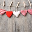 Red hearts hanging over wood background — Stock Photo