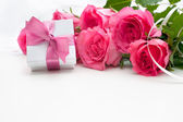 Blumenstrauß aus rosen und geschenk-box — Stockfoto