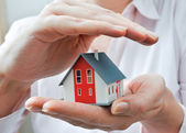 House in human hands — Stock Photo