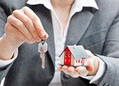 Affärskvinna med hus modell och nycklar — Stockfoto