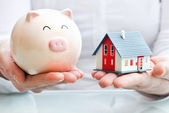 Hands holding a piggy bank and a house model — Stok fotoğraf