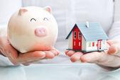 Ruce držící prasátko a model domu — Stock fotografie