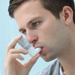 Young man using an asthma inhaler — Stock Photo