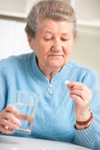 Senior woman taking her medicine — Stock Photo