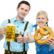 Couple with Oktoberfest beer steins and pretzel — Stock Photo