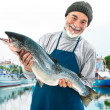 Fisher holding a big atlantic salmon fish — Stock Photo #33059127
